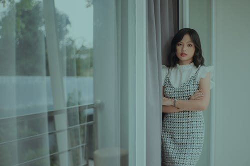 Serious young ethnic woman in stylish dress standing near curtains and window near balcony in daylight and looking at camera with crossed hands