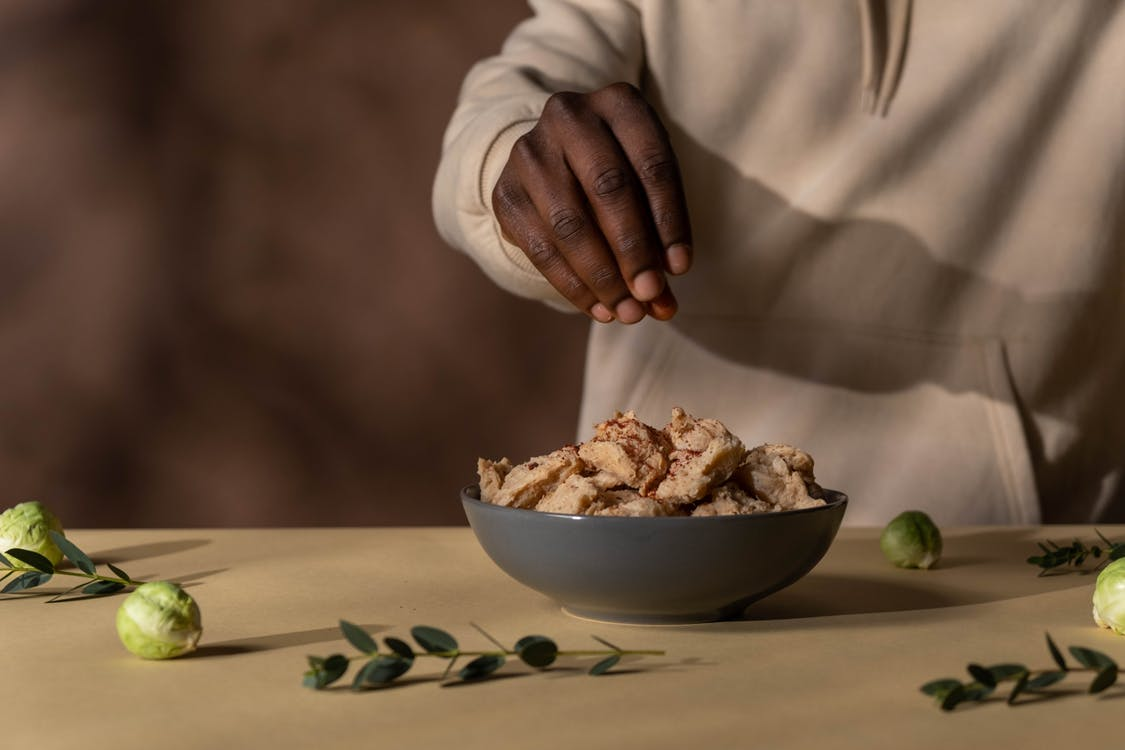 Person Holding White Ceramic Bowl With Brown Food