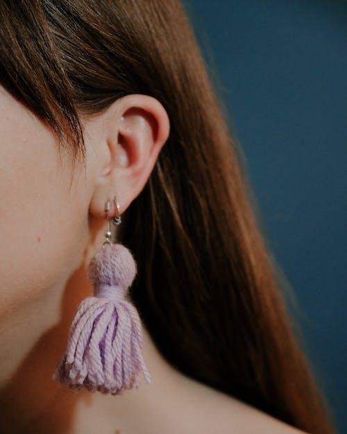 Unrecognizable woman wearing earrings with yarn tassels
