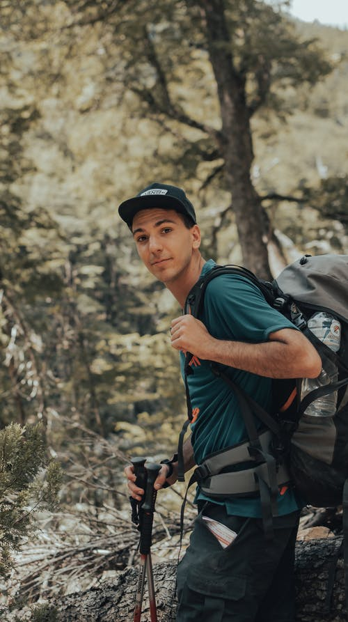 Positive traveler with trekking poles and backpack walking in forest