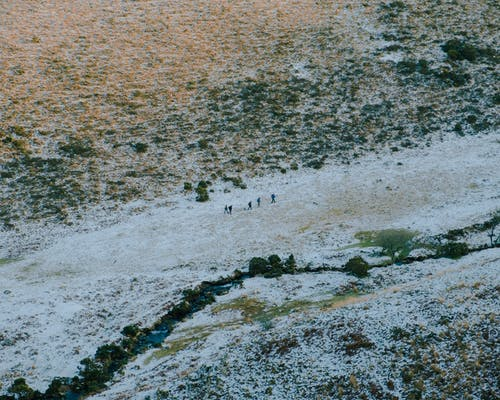 Group of tourists walking on snowy hilly terrain