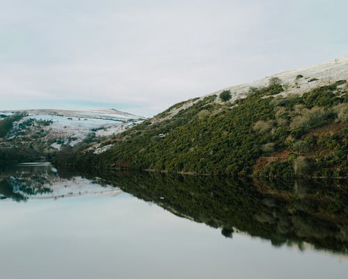 Picturesque view of lake with reflection of grassy slope against snowy hill under cloudy sky