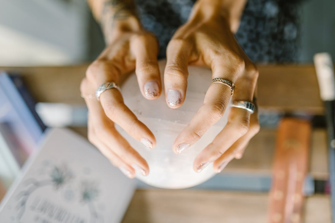 Person Wearing Silver Ring Holding White crystal ball. Magick