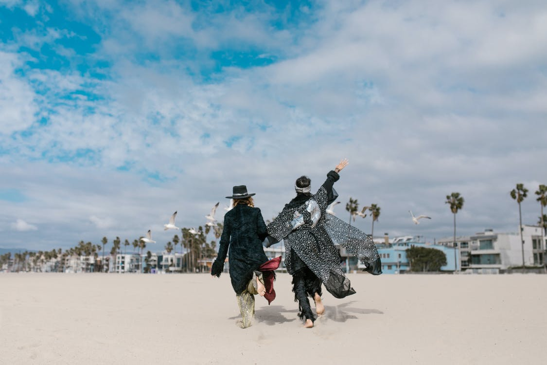 Man and Woman Walking on White Sand Under Blue Sky