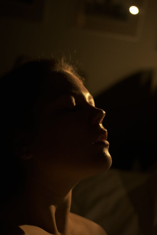 Young woman with bare shoulders and closed eyes in dark room with sunlight on body