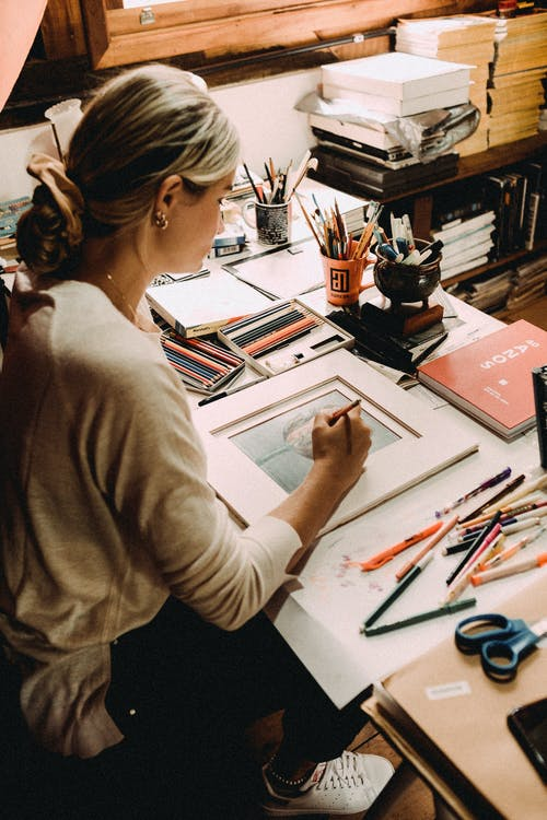 From above of young concentrated woman creating picture at table with many art supplies