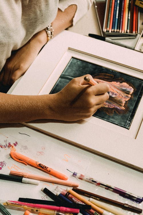 Woman creating picture with pencil at table
