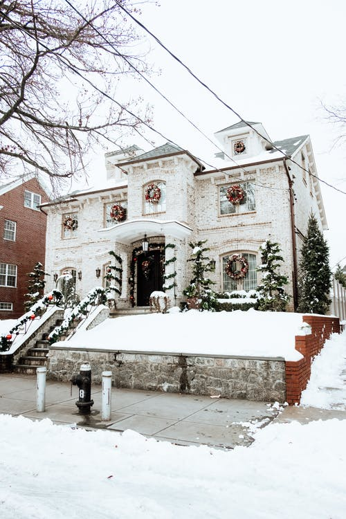 Facade of decorated residential building with wreaths on windows located on snowy street with green firs and staircase in winter day