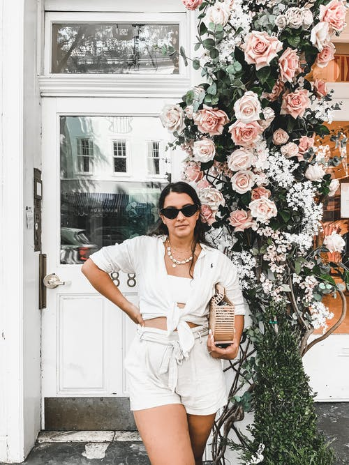 Trendy female in white outfit and sunglasses standing with purchase near blooming flowers growing on bush near entrance of building