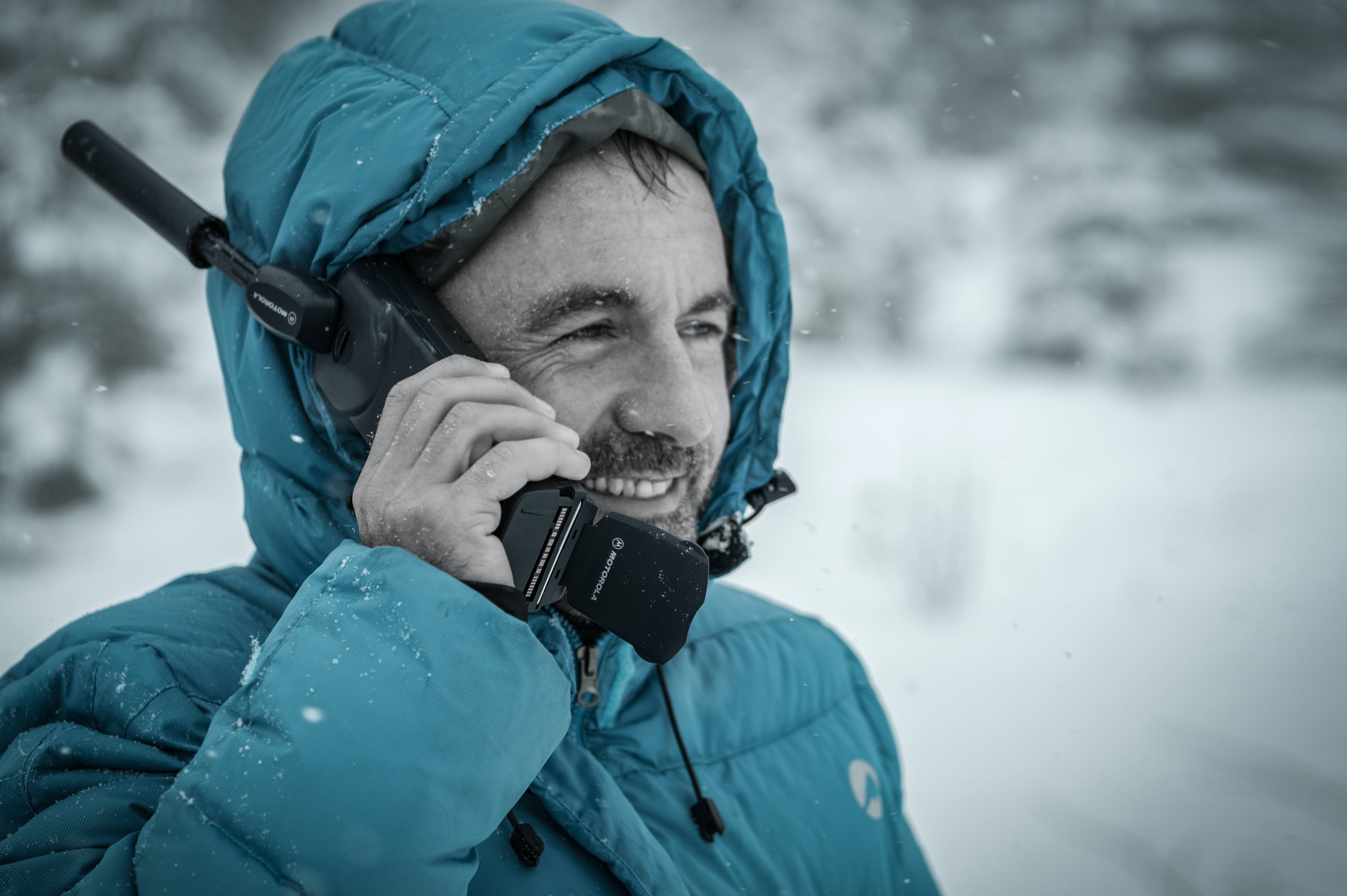 Man in Blue Hoodie Jacket Holding Black Radio Receiver during Snowy Day Time
