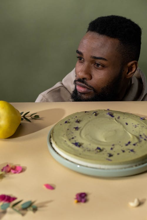 A Man and a Layered Cake on the Table