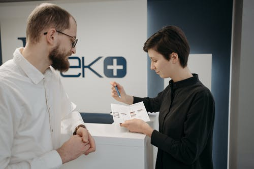 A Woman in Black Long Sleeves Explaining the Services Using a Small Flyer