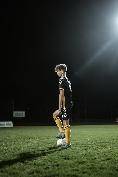 Side view of focused sportive teen male football player in uniform preparing for kicking ball in stadium