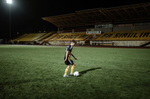 Teen football player running with ball in stadium