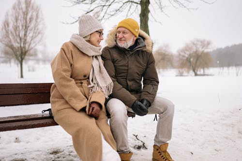 An Elderly Couple Sitting on the Park Bench in Winter
