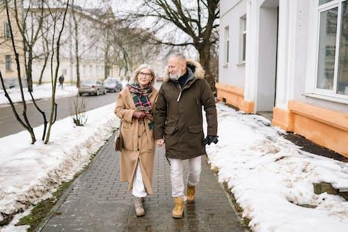 An Elderly Couple Walking on the Sidewalk