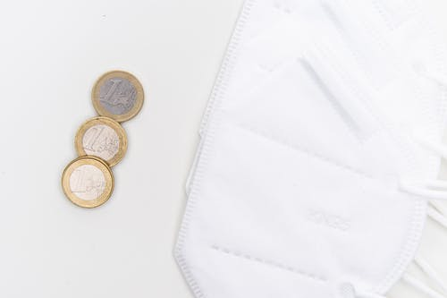 2 Silver and Gold Coins on White Surface