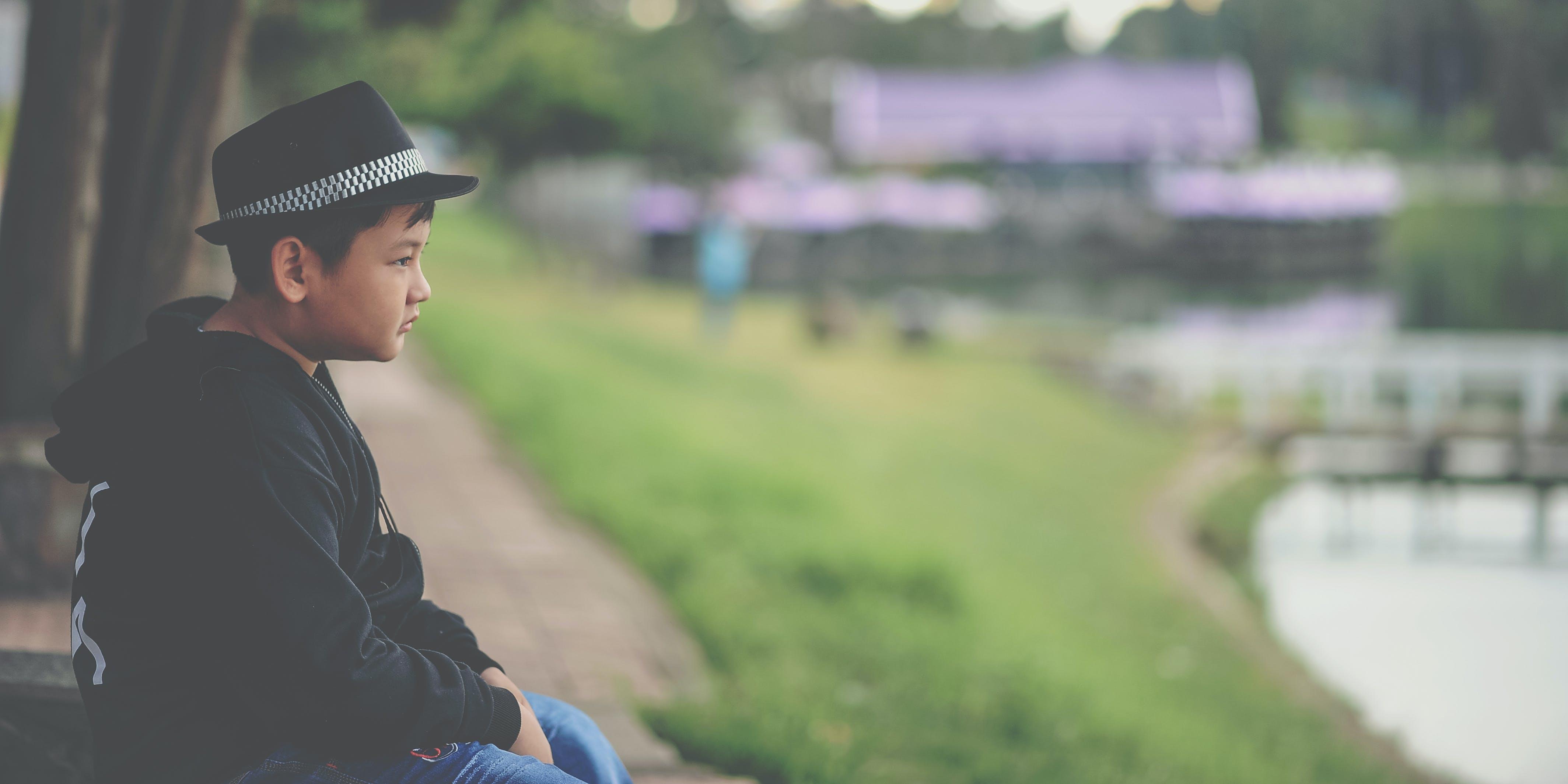 Boy in Black Jacket and Black Fedora Hat Sitting Near Body of Water