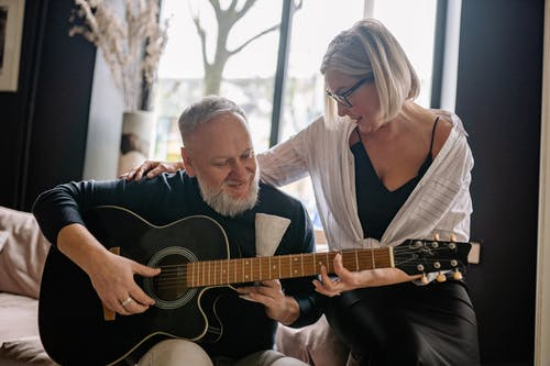 An Elderly Couple Playing the Guitar Together