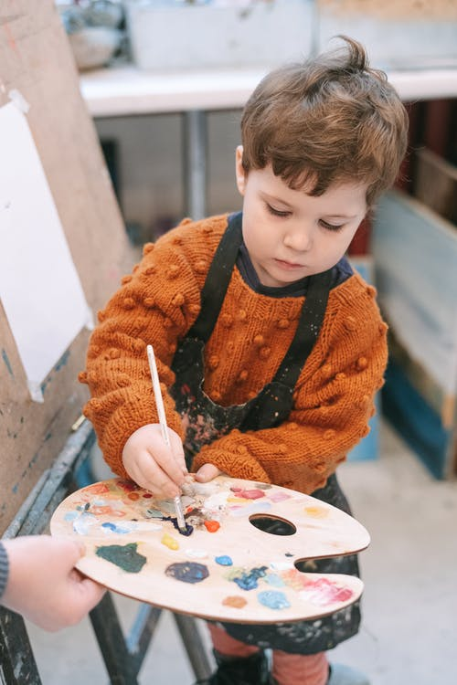 A Boy Learning How to Paint