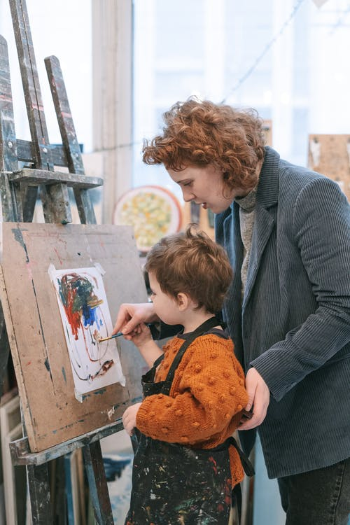 A Woman Teaching a Boy the Art of Painting
