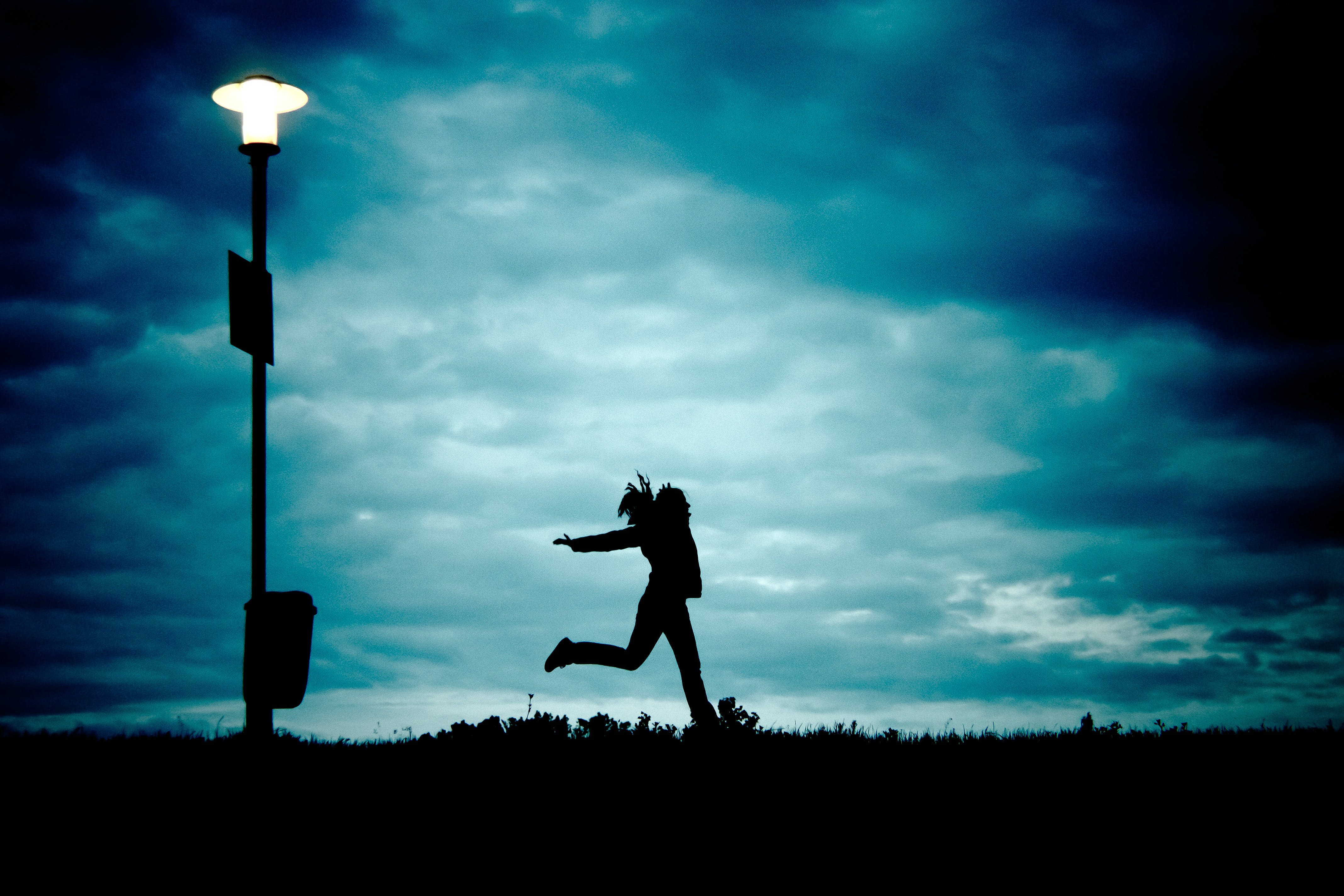Silhouette of Person Beside Silhouette of Street Light