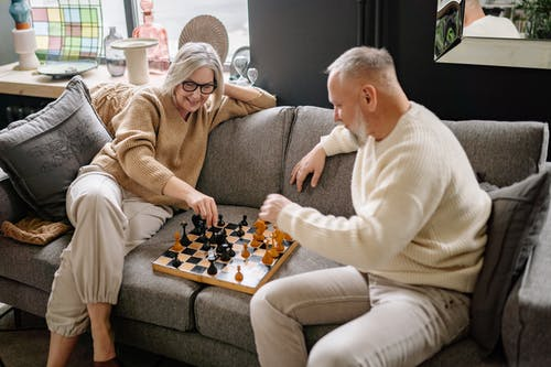 2 Women Sitting on Couch Playing Chess