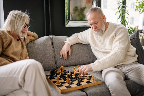 Man in White Sweater Playing Chess