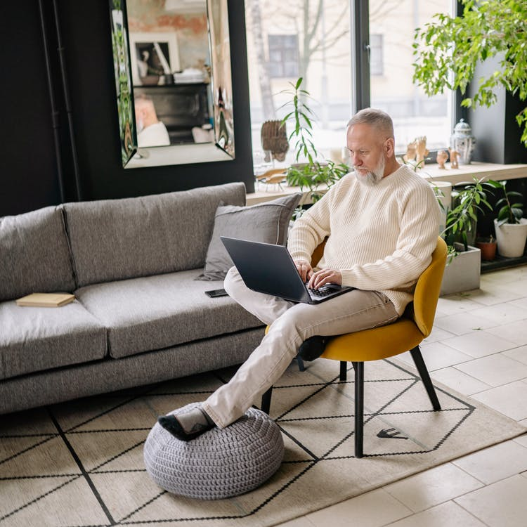 Man in White Dress Shirt Sitting on Gray Couch Using Macbook