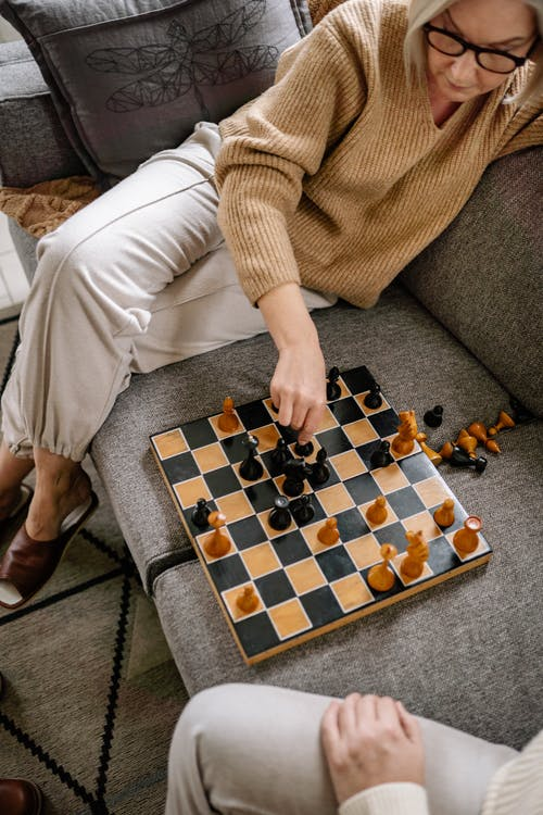 Person Playing Chess Game on Black and White Checkered Table Cloth