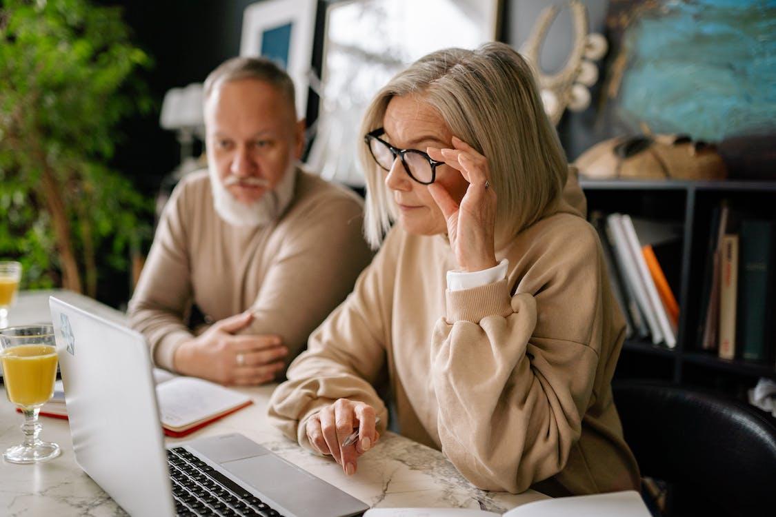 Man in Brown Sweater Sitting Beside Woman in Brown Sweater