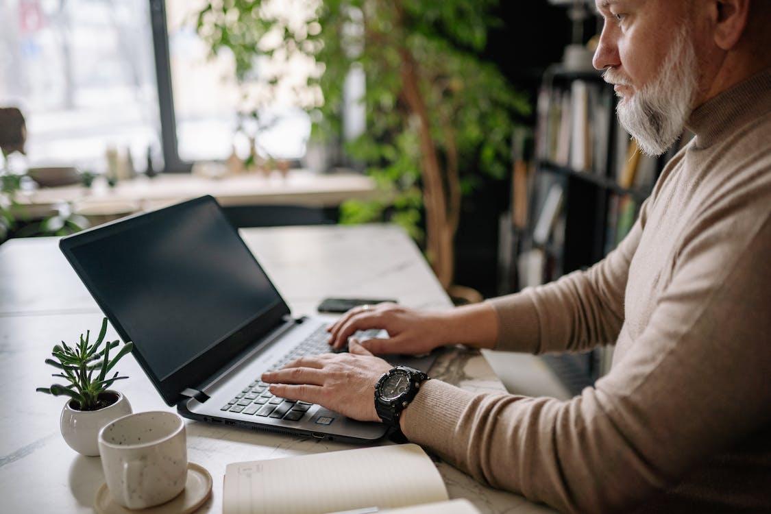 Man in Gray Long Sleeve Shirt Using Black Laptop Computer