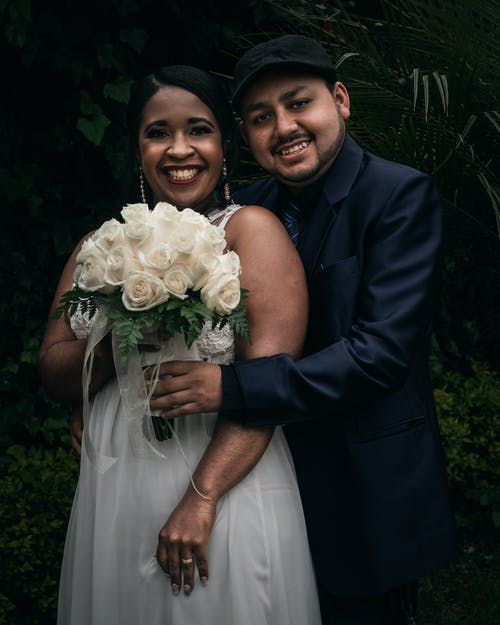 Man in Black Suit Jacket Beside Woman in White Wedding Dress Holding Bouquet of White Roses