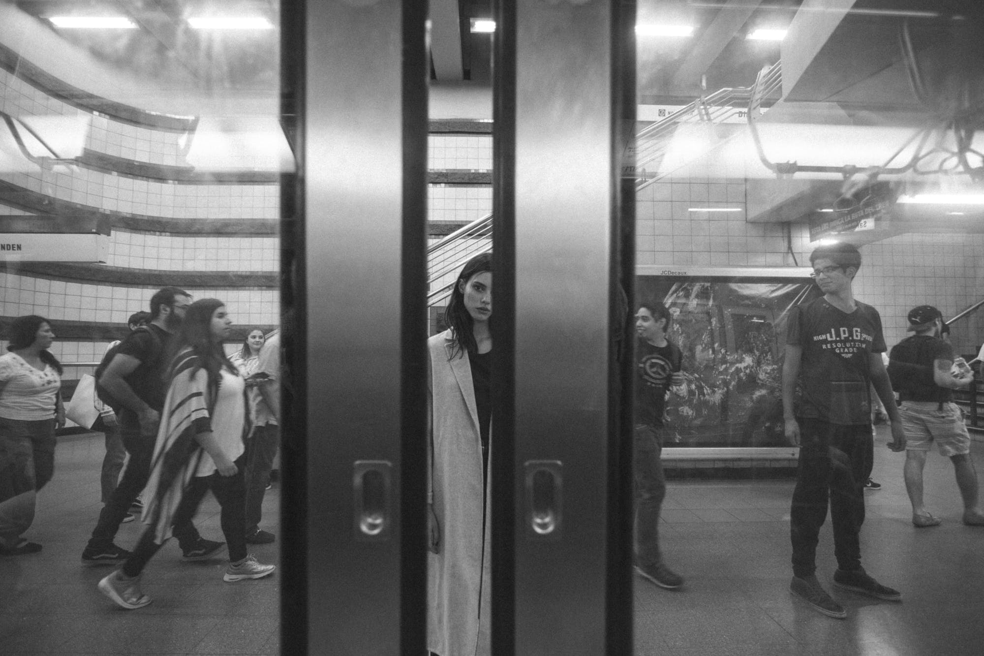 Monochrome Photography of Woman Standing at the Subway
