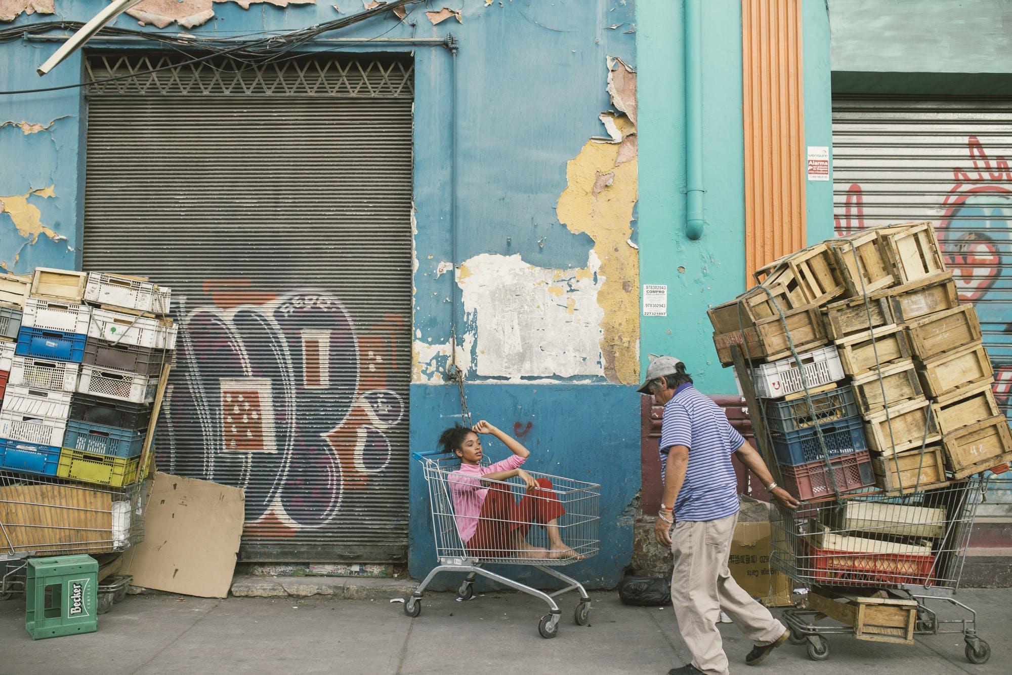 Man Wearing Gray Cap and Blue Shirt Holding Shopping Cart