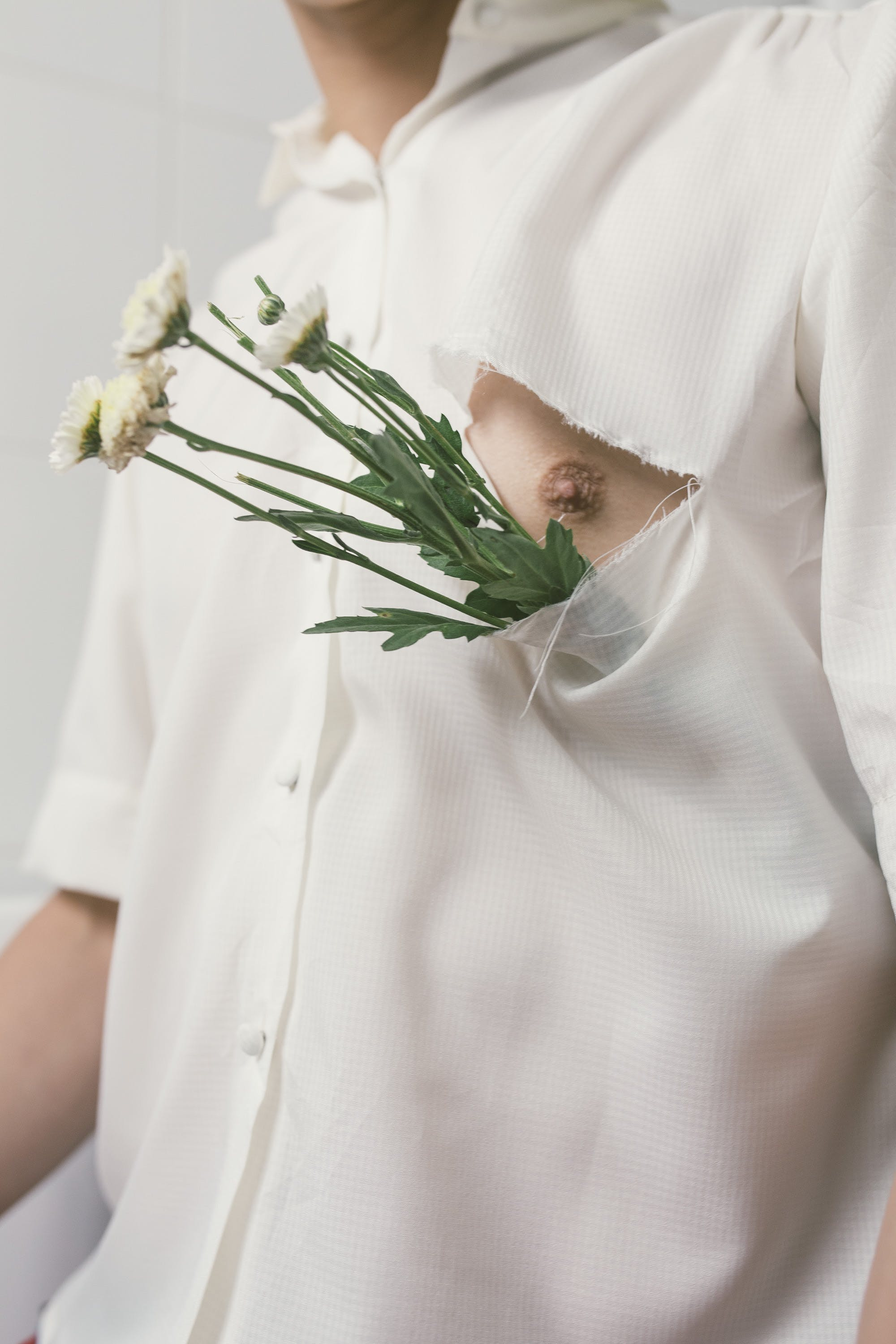 Man in White Button-up Shirt With White Flowers