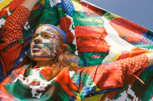 Woman With Face Paint Raising Her Hands Holding Textile