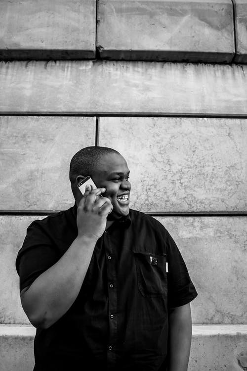 Smiling Man Talking on Cellphone while Looking to His Side