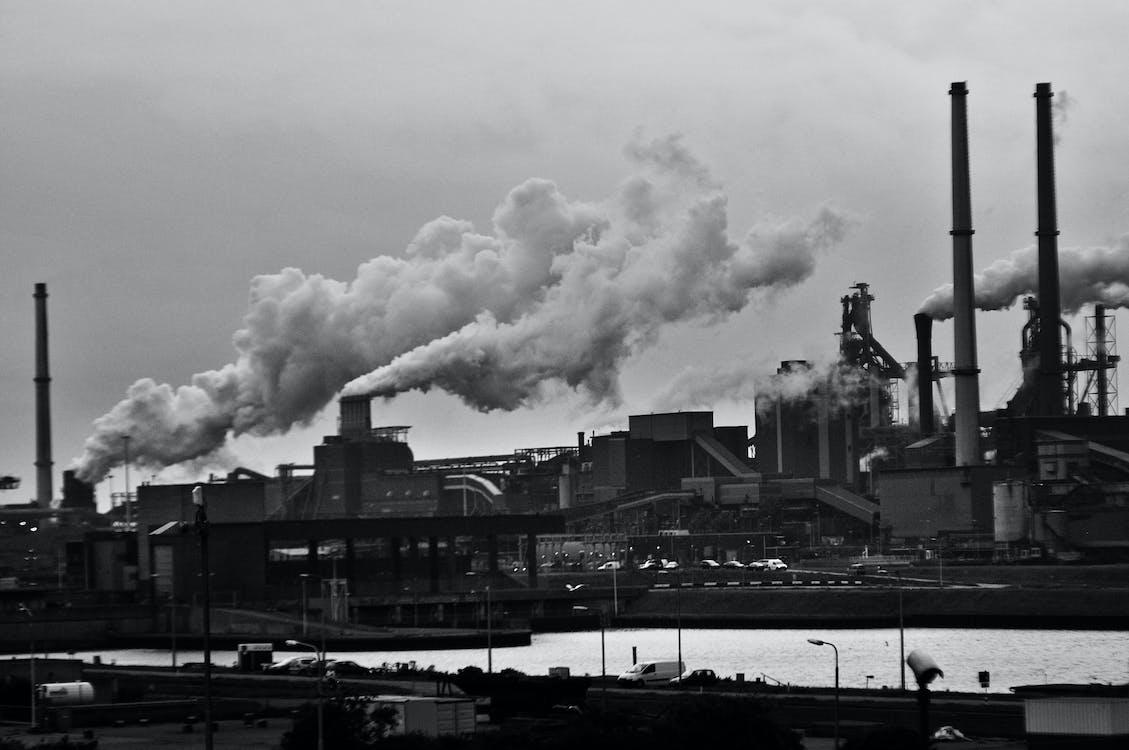 機車在工廠旁邊的灰度攝影