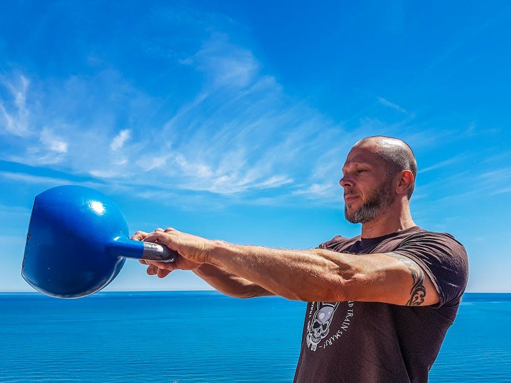 Man Wearing Black Shirt Holding Kettle Bell Near Body of Water