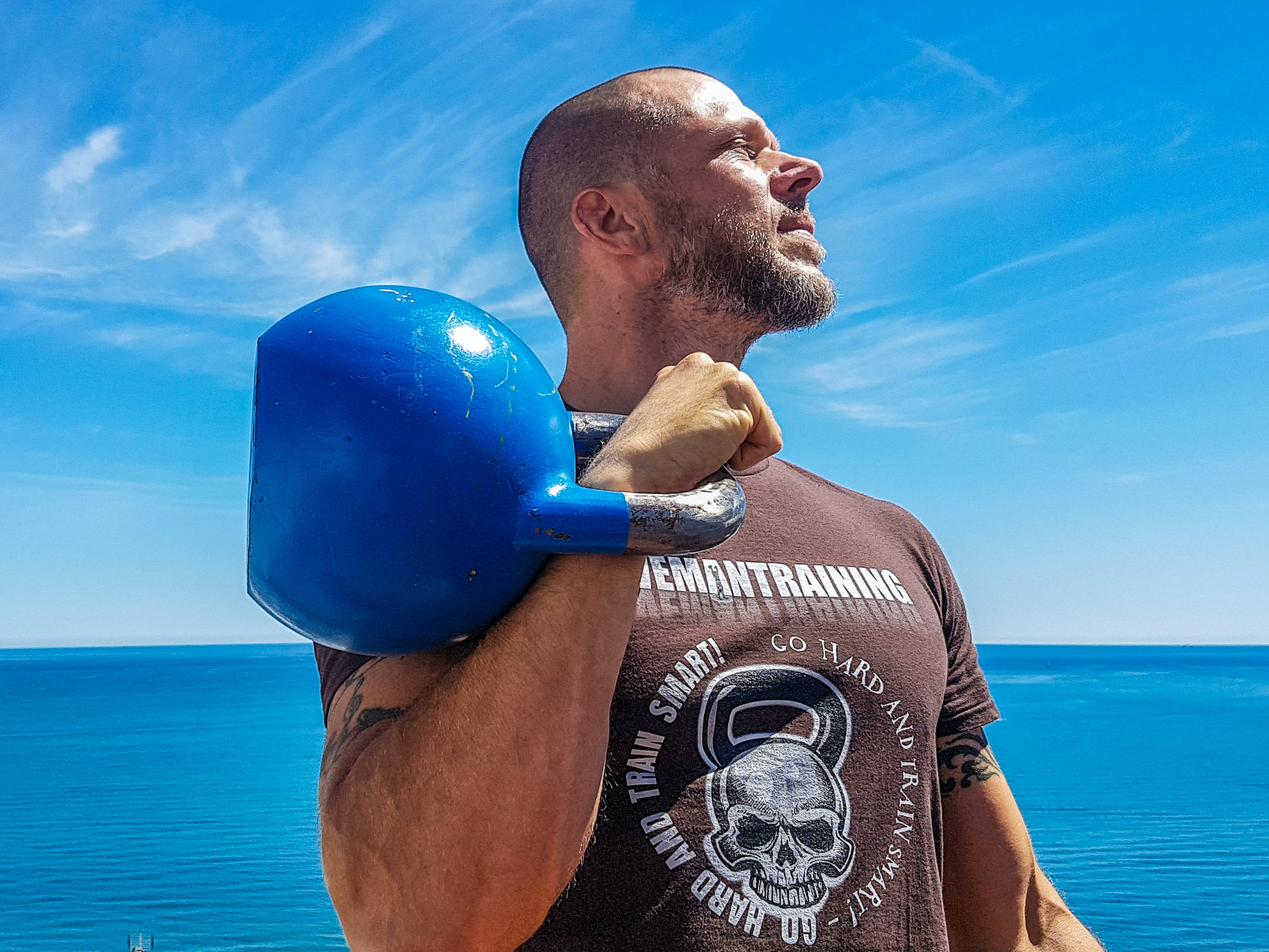 Man Carrying Kettlebell Near Body of Water