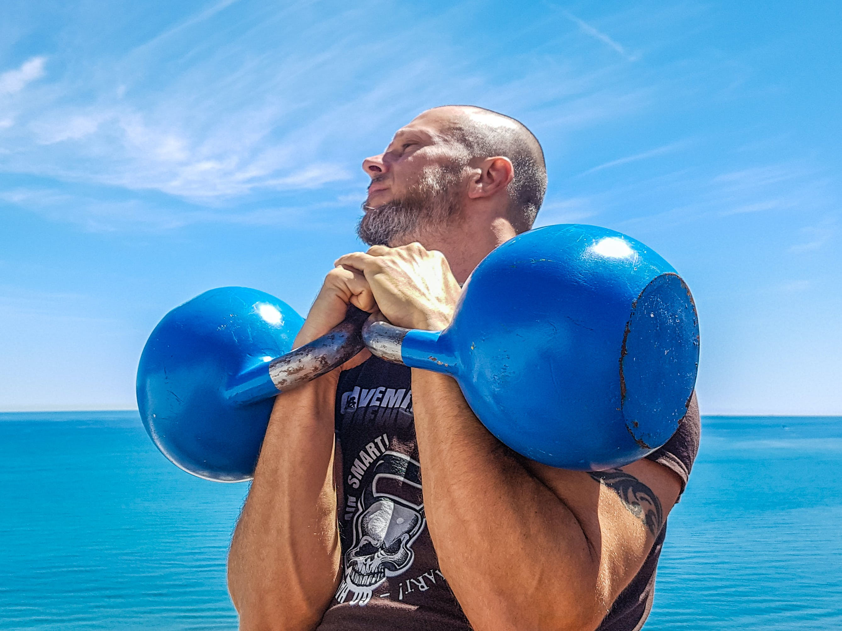 Man Lifting Pair of Blue Kettlebells