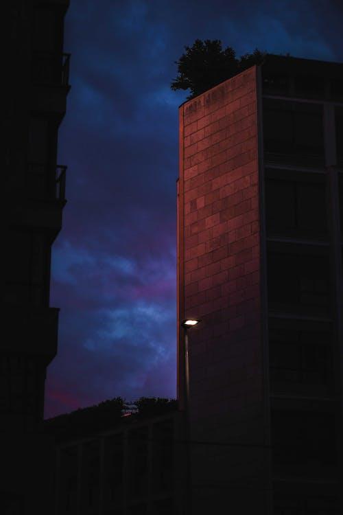 Stone multistory buildings under dark cloudy sky