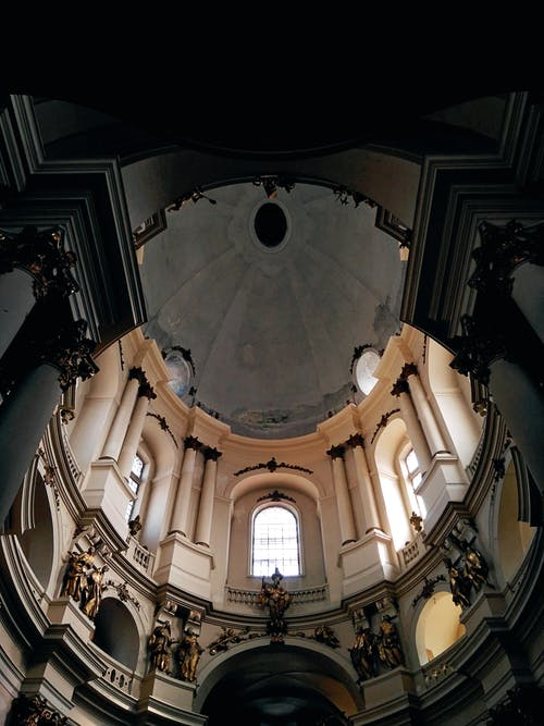 From below interior of aged Dominican Church with arched windows and ornamental walls under dome located in Lviv
