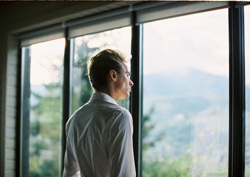Thoughtful young stylish guy standing near window at home