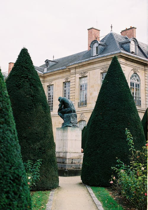 Exterior of aged Musee Rodin with well groomed garden with green trees and sculpture against cloudy sky in Paris