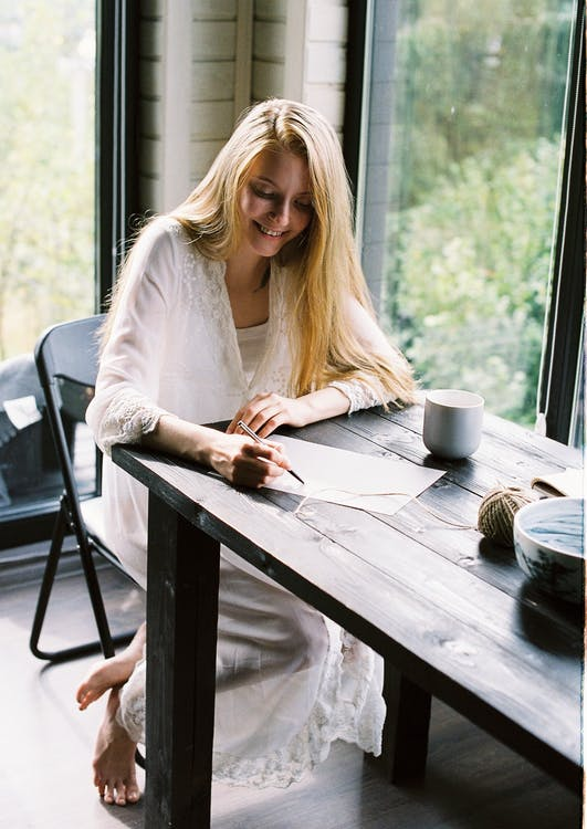 Full body of happy young female with long blond hair in stylish white dress smiling while sitting at table in cozy house and writing letter