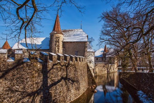 Old stone castle facade reflecting in city river