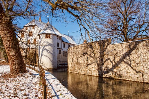 Medieval stone fortress with building exterior against rippled water and leafless trees in city on sunny day