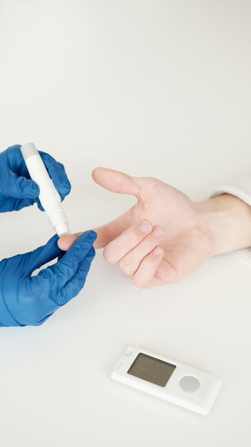 Person in Blue Gloves Holding White Tube